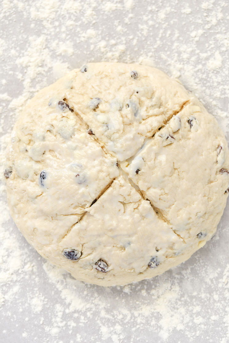 A loaf of Irish Soda Bread with an 'X' cut in the top.