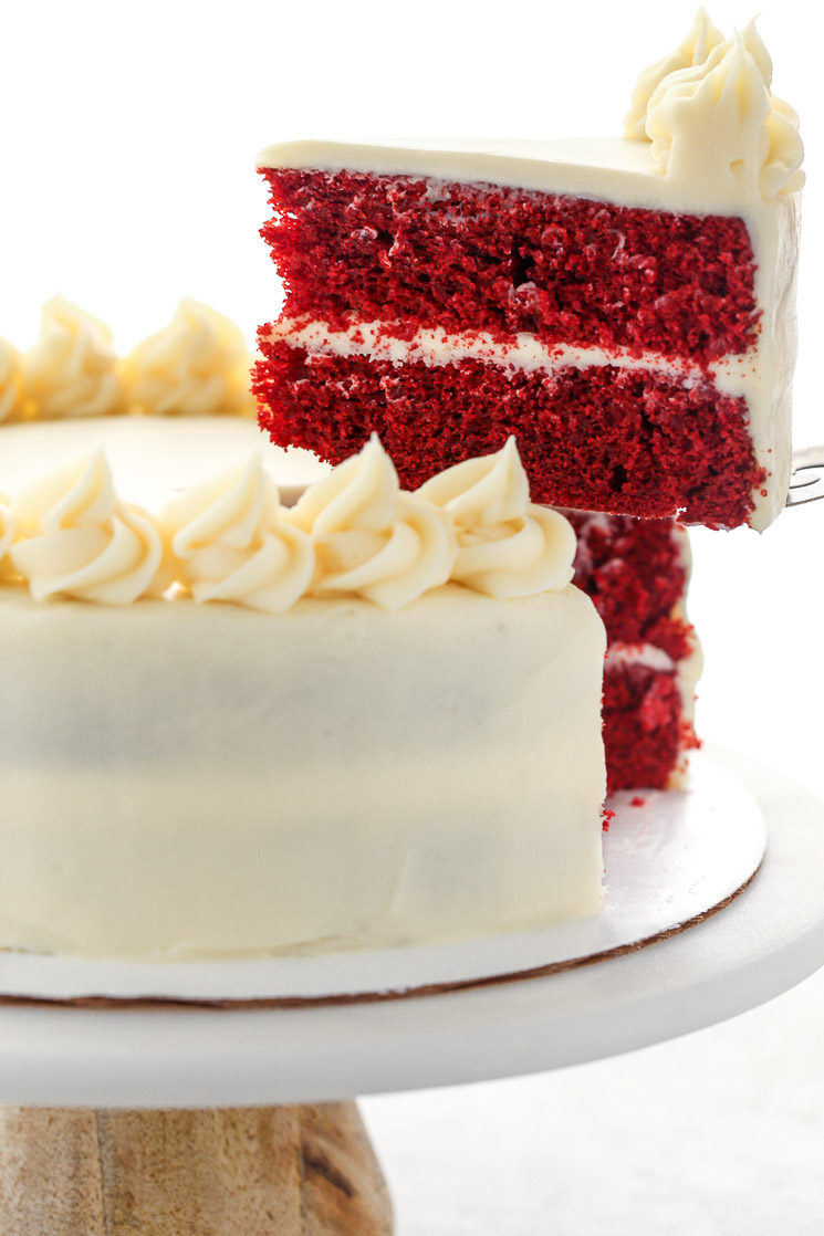 A slice of red velvet cake being removed from the full cake on a marble cake stand.