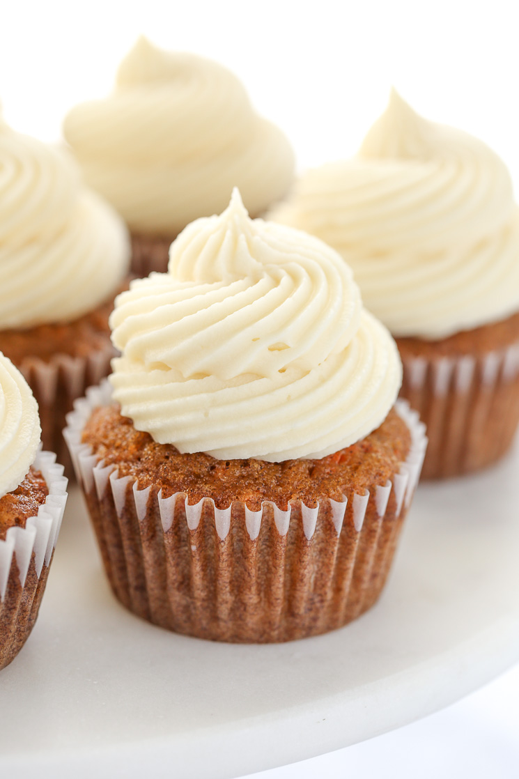 A close up picture of carrot cake cupcakes topped with cream cheese frosting sitting on top of a marble cake stand.