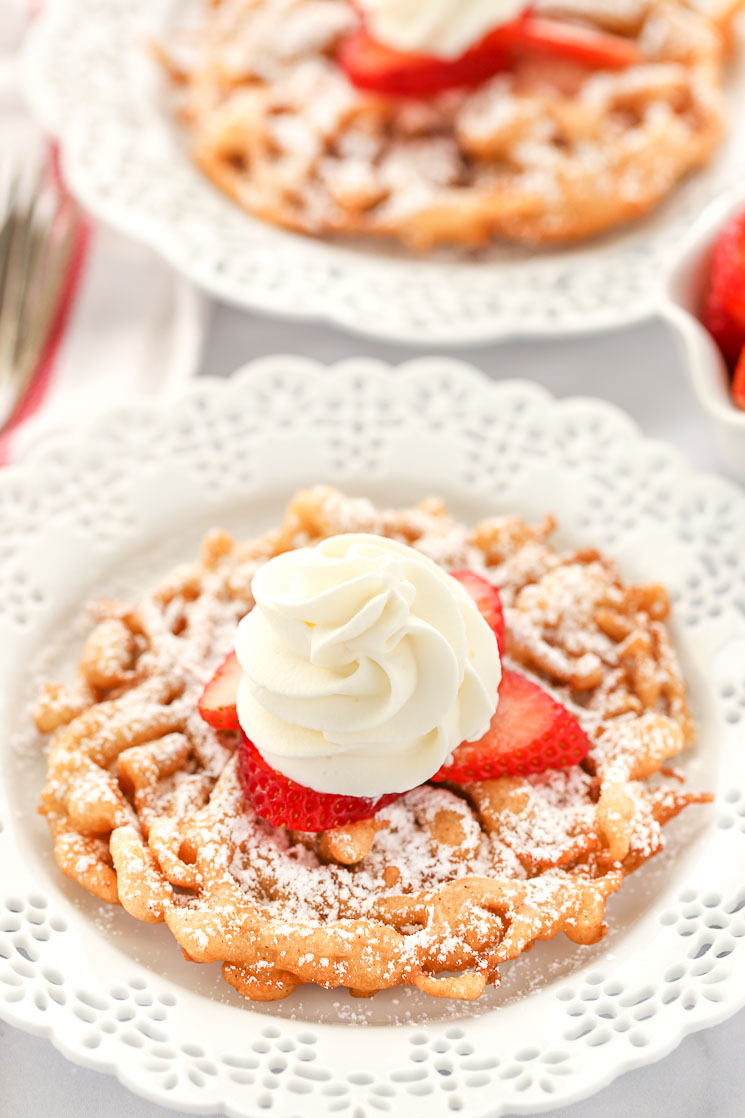 Two funnel cakes topped with powered sugar, strawberries, and homemake whipped cream sitting on decorative white plates.