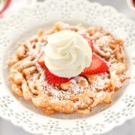 A funnel cake topped with strawberries and homemade whipped cream sitting on a decorative white plate.