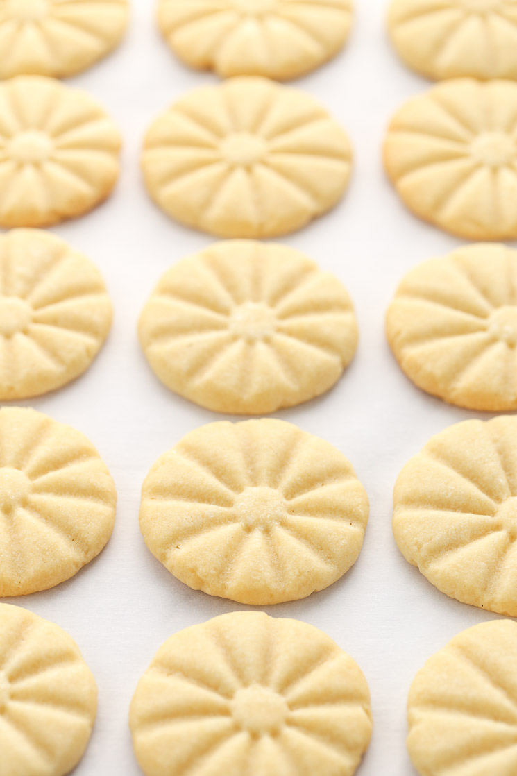 A baking sheet covered in parchment paper topped with shortbread cookies right out of the oven.