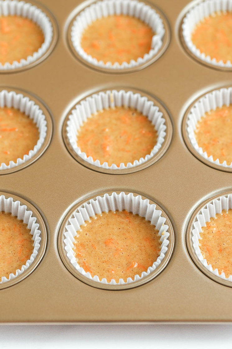 A muffin pan filled with cupcake liners and carrot cake cupcake batter.