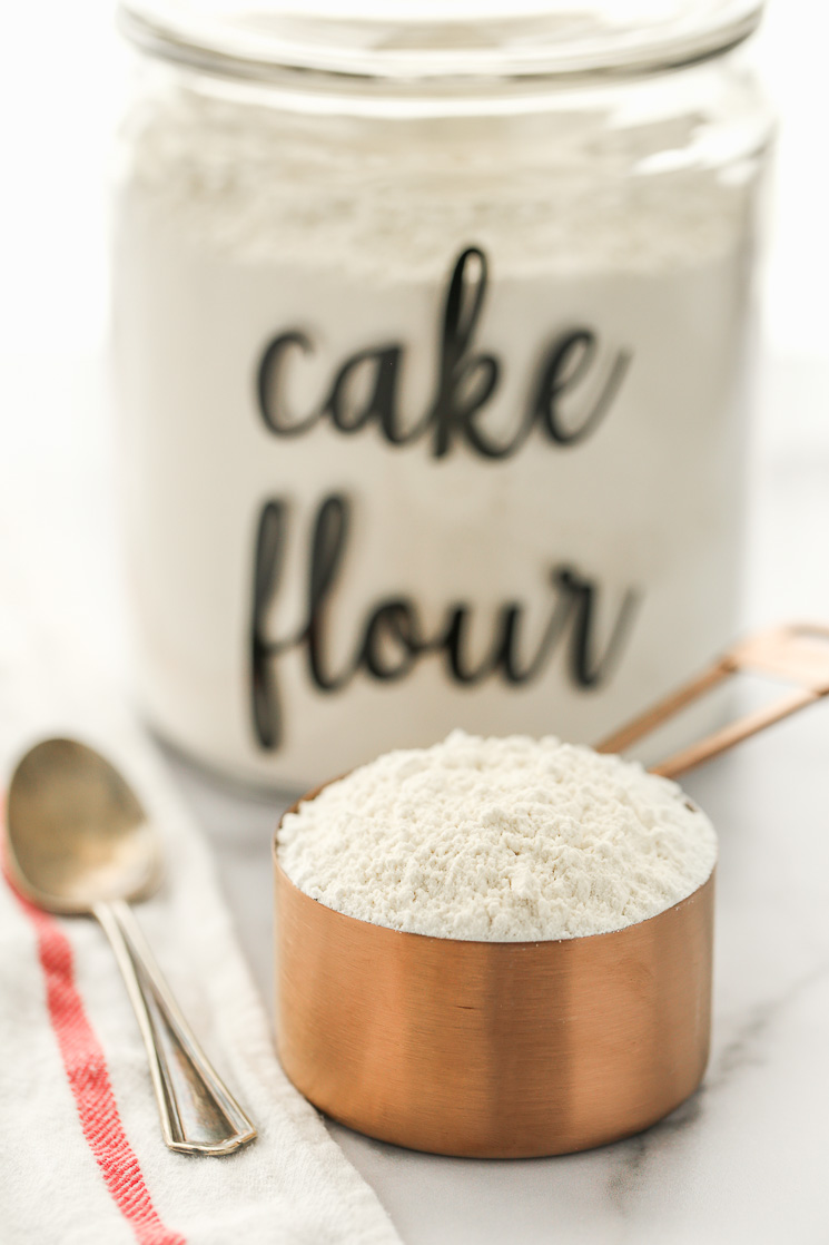 A copper measuring cup filled with cake flour and a container of flour in the background.
