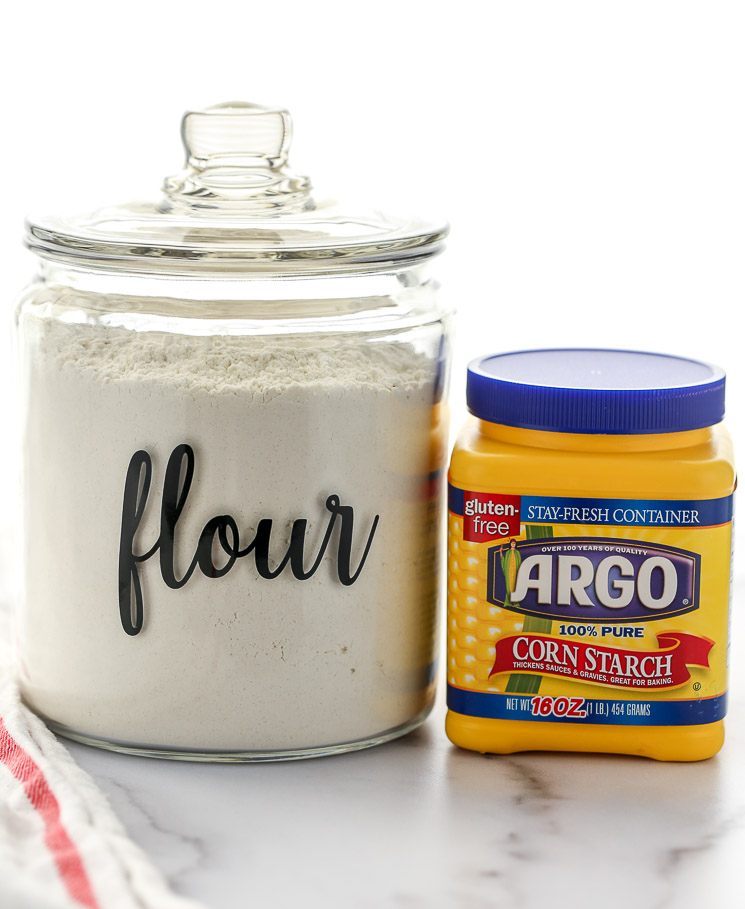 A container of cake flour and cornstarch sitting on top of a marble surface.