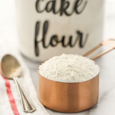 A close-up picture of a copper measuring cup filled with cake flour.