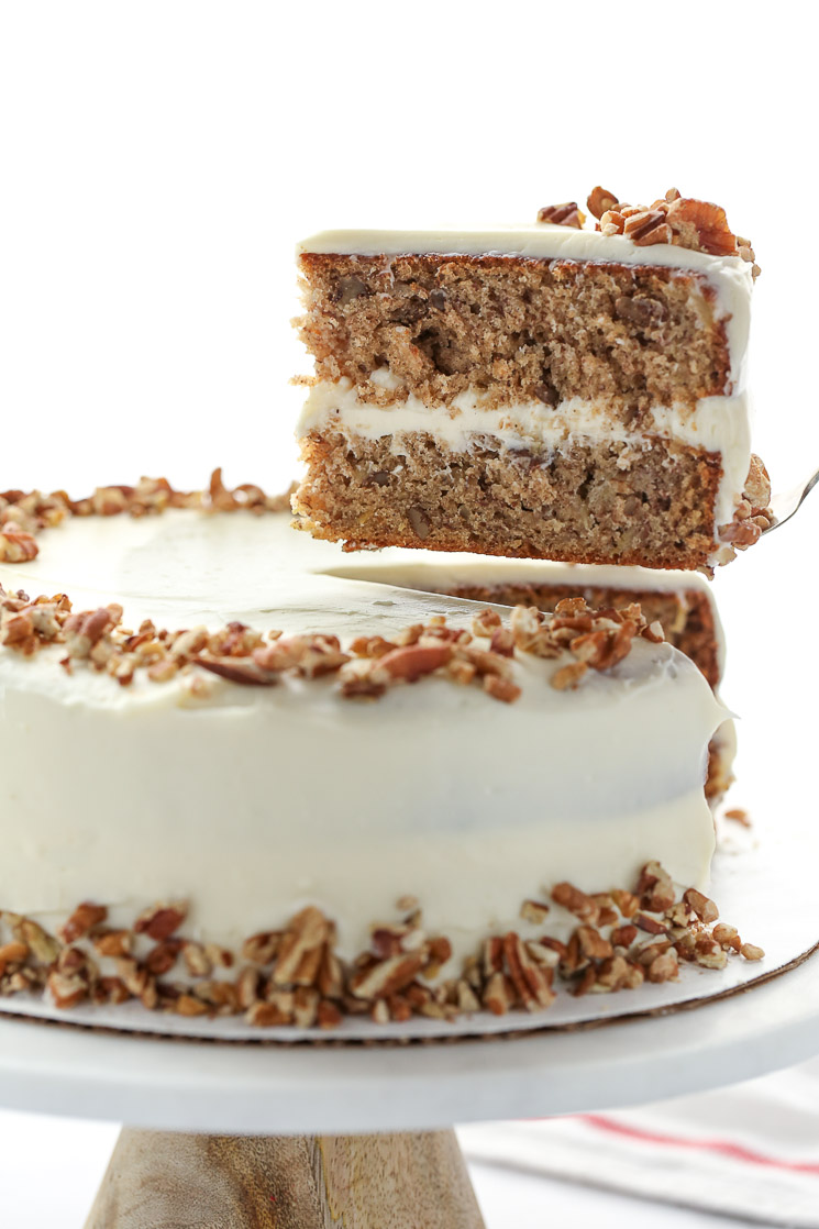A whole hummingbird cake on top of a marble cake stand with one piece being removed to show the cake layers.