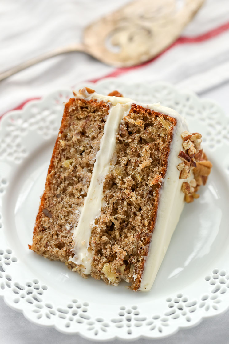 A slice of hummingbird cake on a decorative white plate with a cake server in the background.