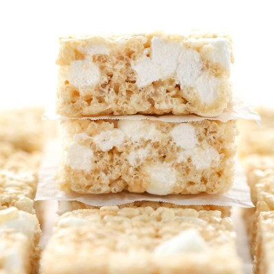 A close-up picture of a stack of rice krispie treats with more rice krispie treats around it.