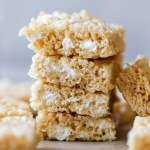 A stack of Rice Krispie treats on top of a wooden tray.