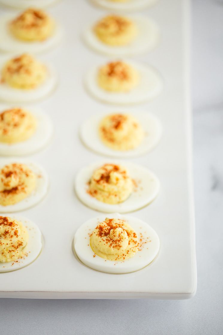 Deviled eggs topped with smoked paprika in a deviled egg tray.