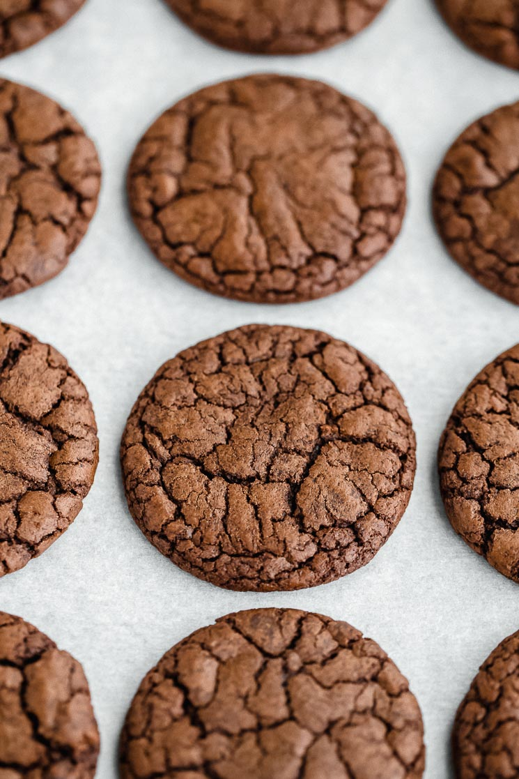 Baked cookies lined up on a baking sheet lined with parchment paper.