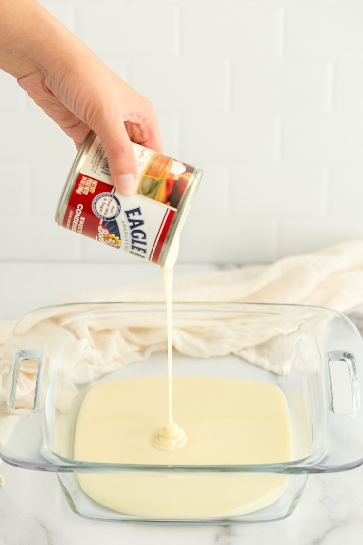 A can of sweetened condensed milk being poured into a clear baking dish.
