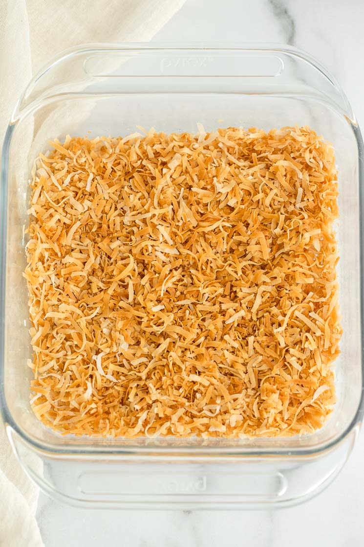 A glass baking dish with toasted coconut covering the bottom.