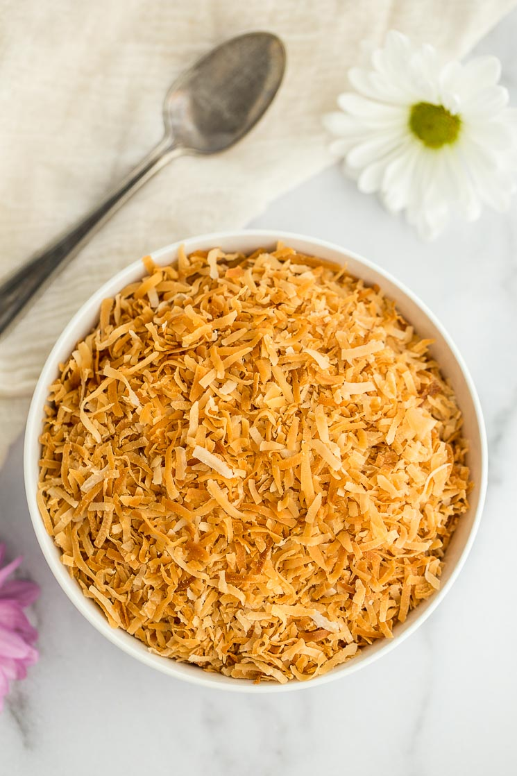 A white bowl filled with toasted coconut with an antique spoon and flowers in the background.