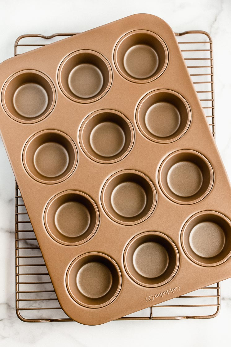 A muffin pan and cooling rack stacked on top of each other on top of a marble surface.