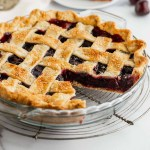 A cherry pie sitting on a wire rack with a slice taken out of it.