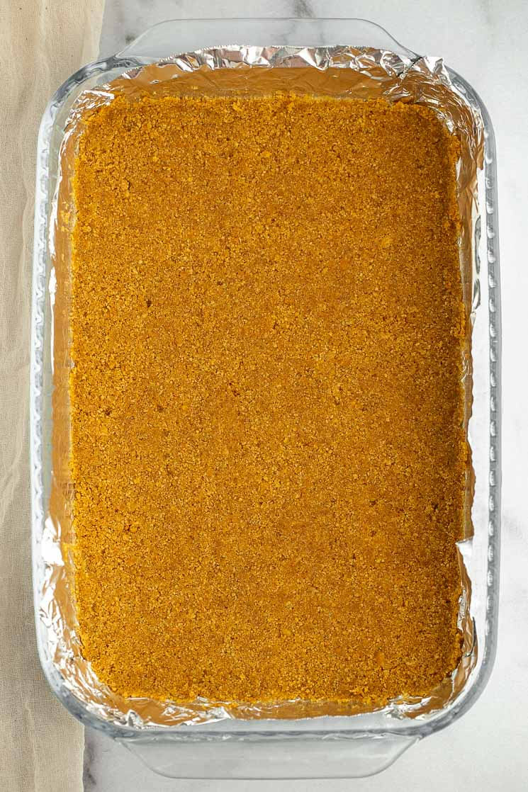 A graham cracker crust in a 9x13 pan lined with aluminum foil.