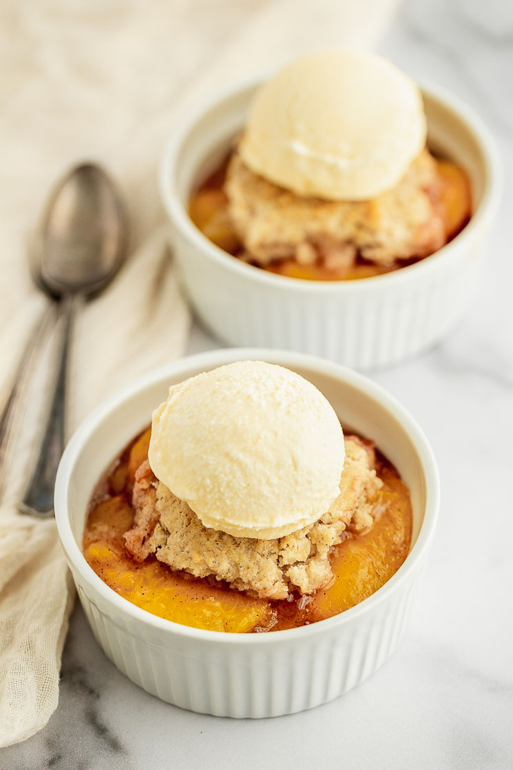 A white ramekin on a marble surface filled with peach cobbler and scoop of ice cream on top.