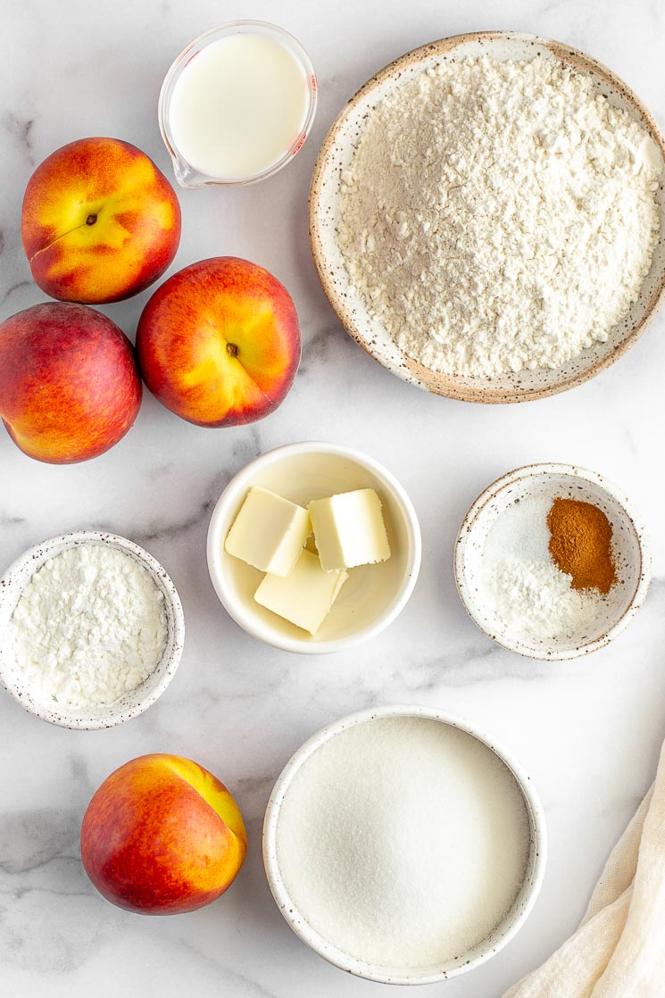The ingredients for peach cobbler in various bowls and plates on a marble surface.