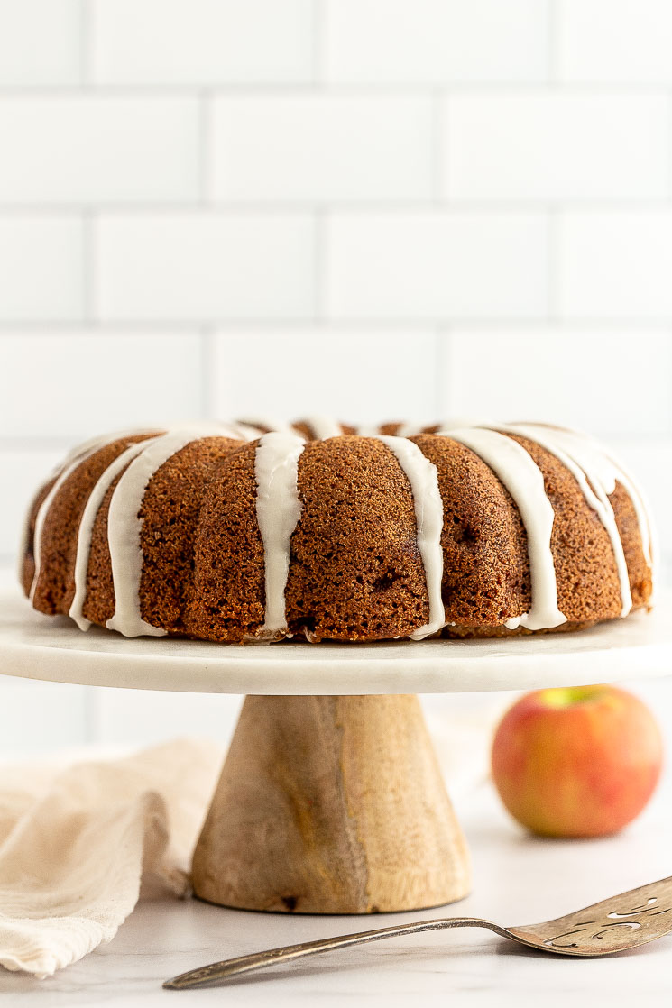 An apple cake sitting on top of a marble cake stand.