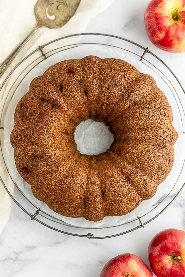 An apple cake sitting on top of a round wire rack.