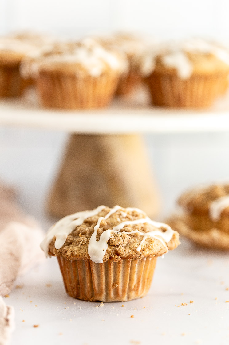 A close-up of an apple muffin with more muffins on a cake stand behind it.