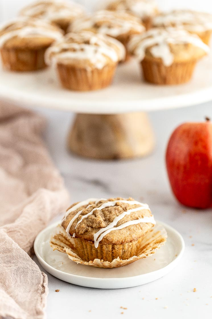 A close-up of an apple muffin on a white plate with the liner peeled away.