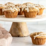 Apple muffins on top of a marble cake stand.