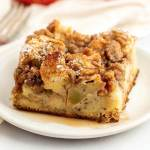 A slice of apple streusel french toast casserole topped with pure maple syrup on a white plate.