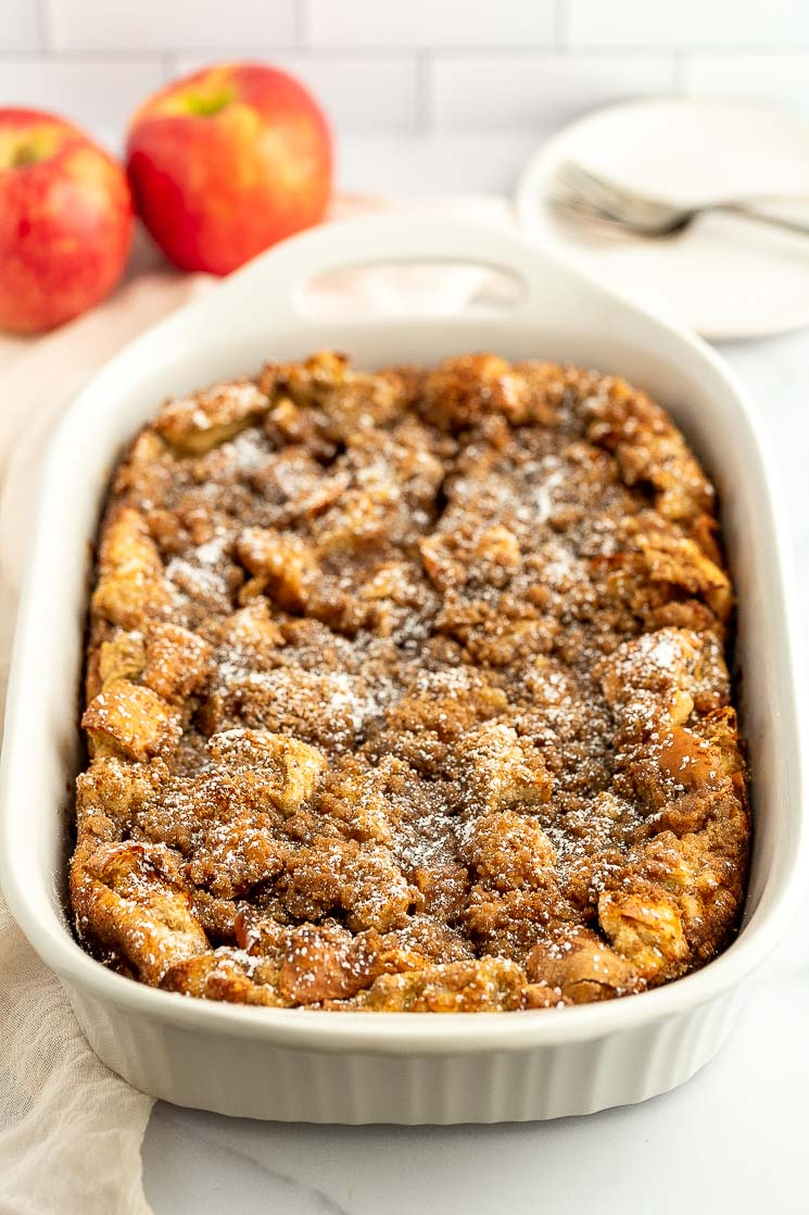 Baked apple streusel french toast casserole in a white baking dish.