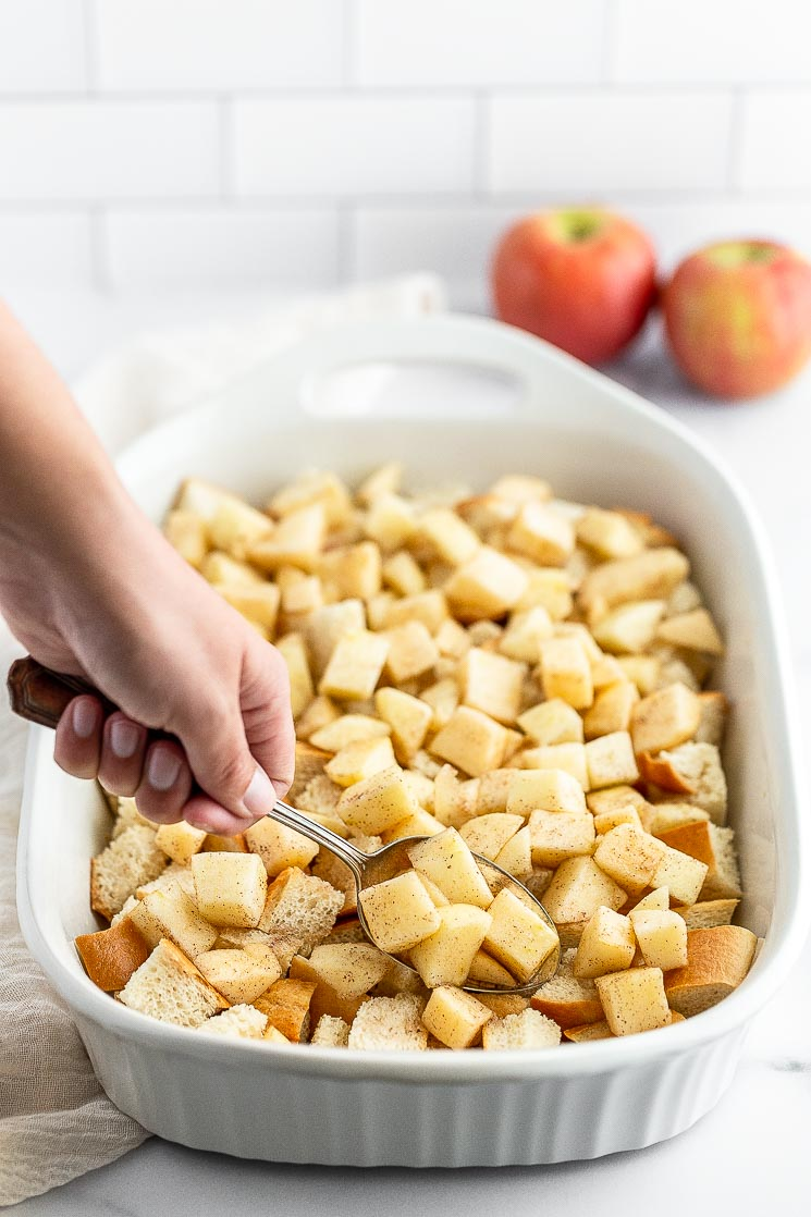 Chopped apples being adding on top of cubed bread in a baking pan.