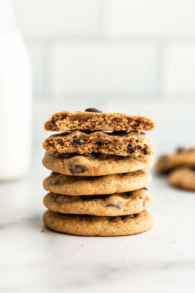 A stack of pumpkin chocolate chip cookies with milk in the background.