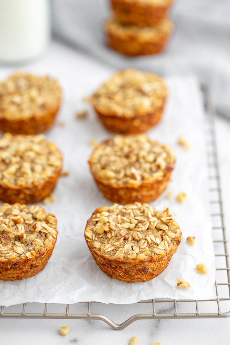 A cooling rack lined with parchment paper with multiple banana baked oatmeal cups on top.