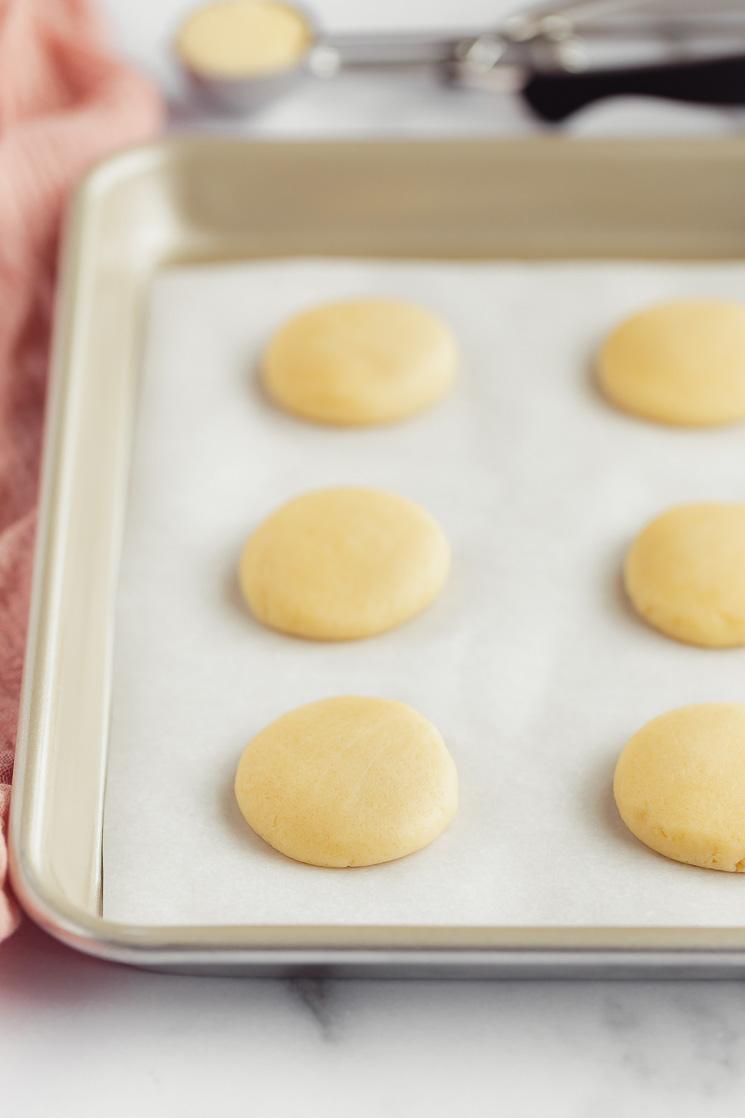 Bolas de massa de biscoito de açúcar, numa forma metálica forrada com papel de pergaminho, achatadas e prontas para ir ao forno.