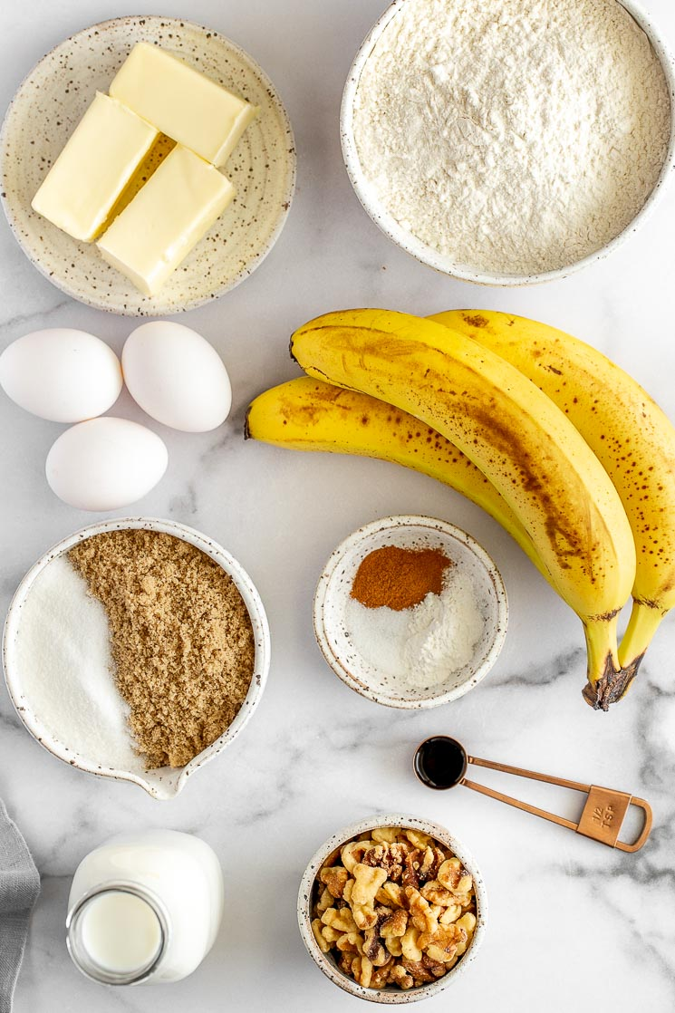 All of the ingredients needed to make a banana cake on a marble surface.