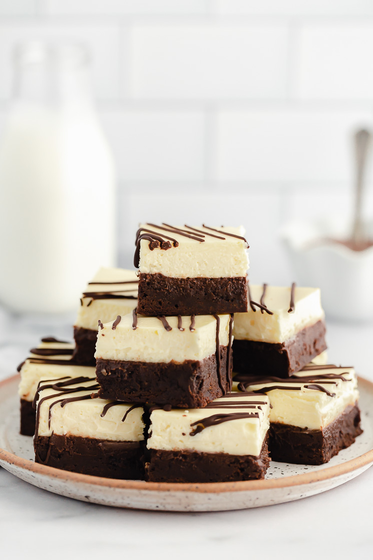 A stack of cheesecake brownies drizzled with chocolate on a rustic clay plate.
