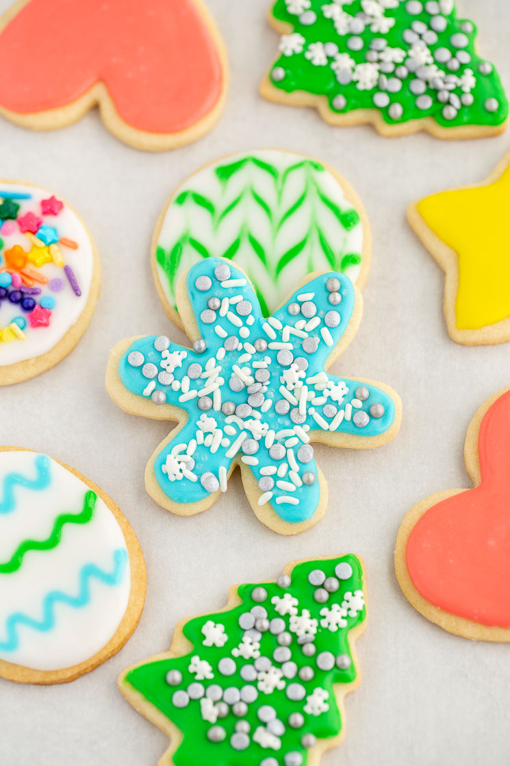 A beautifully decorated group of cut-out sugar cookies spread out on parchment paper.