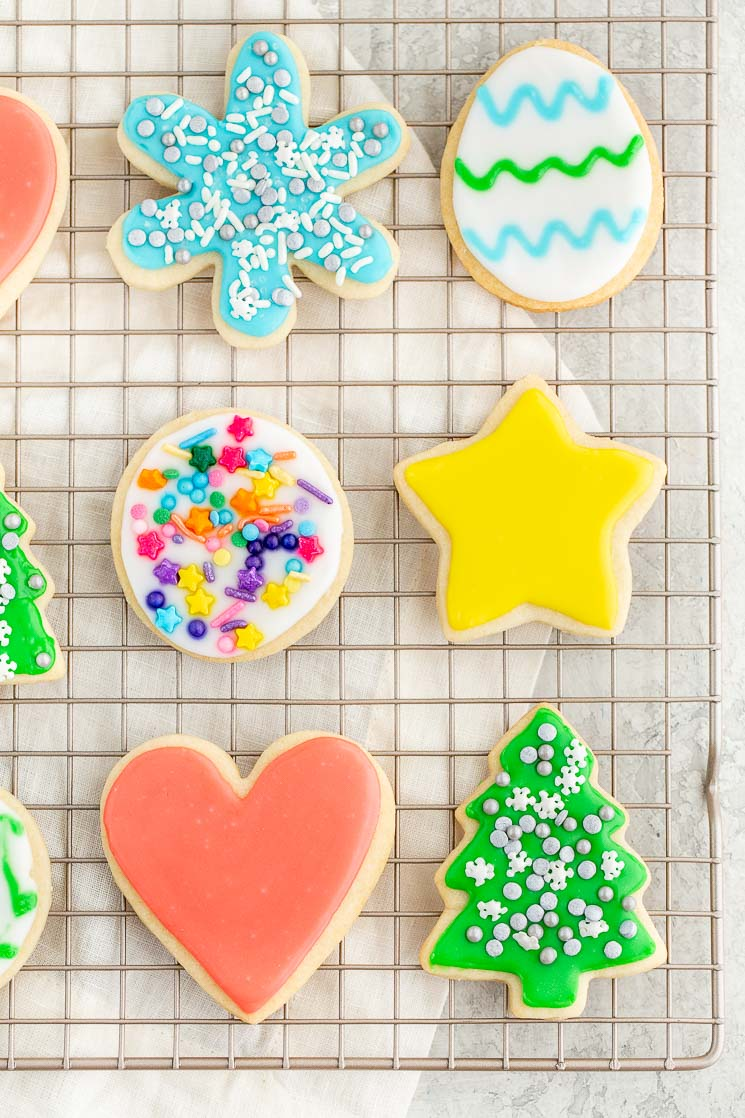 Several different decorated sugar cookies on top of a cooling rack.