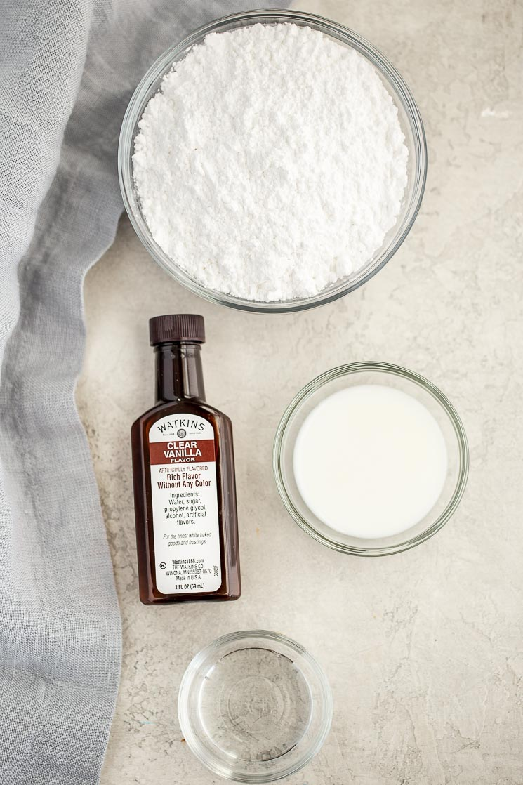 All of the ingredients needed to make easy sugar cookie icing laid out on a rustic concrete surface.