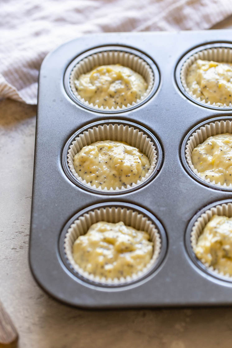 A muffin pan holding batter in muffin liners.