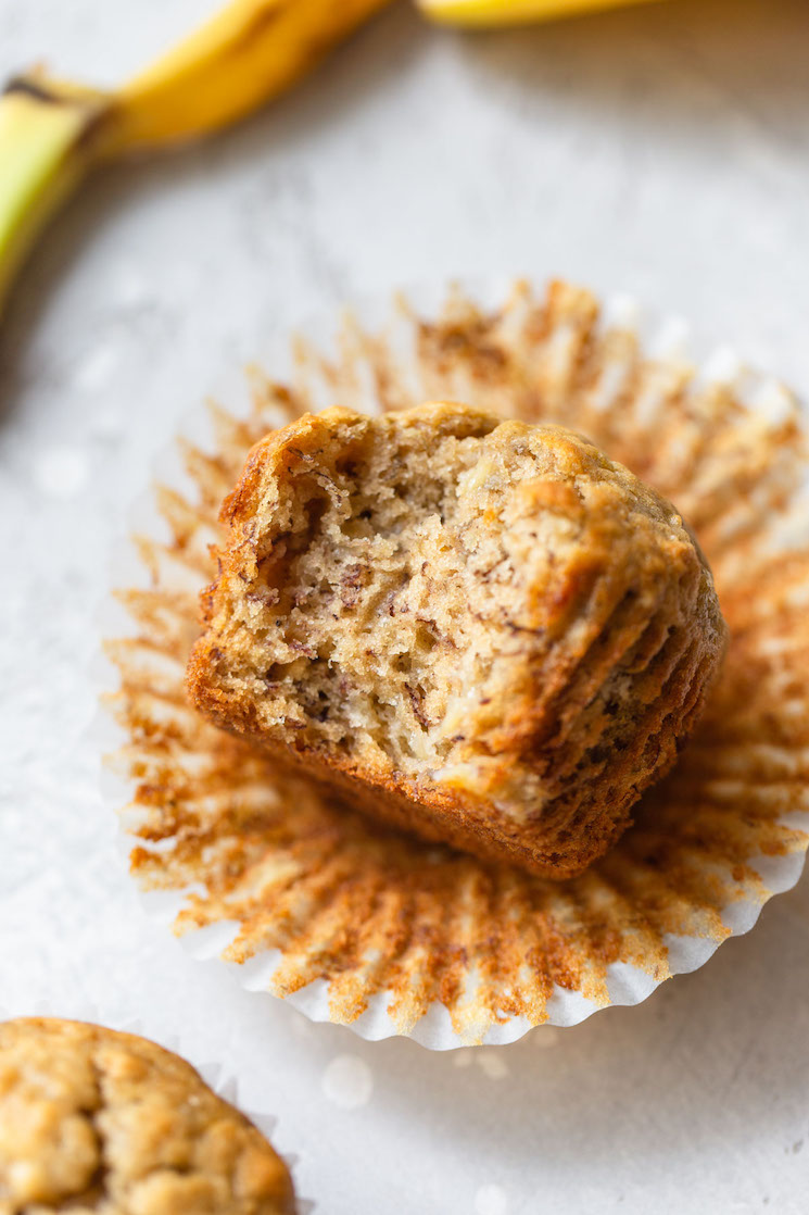 A single banana muffin resting in its wrapper on its side with a bite taken out.