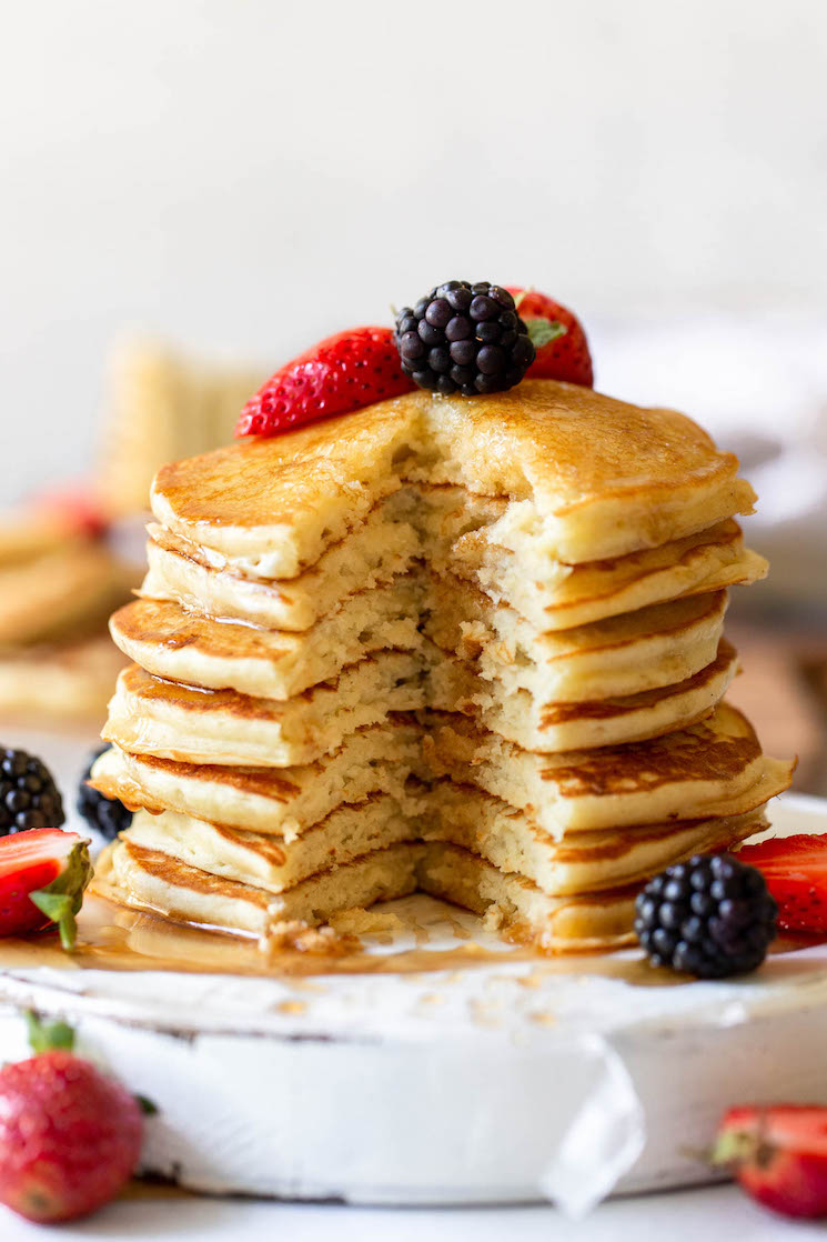 A stack of pancakes topped with syrup and berries and a bite cut out of the whole stack to show the fluffy texture.
