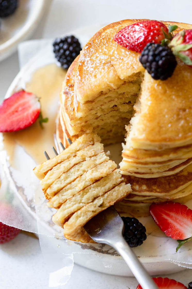 A stack of pancakes topped with berries and syrup with a bite cut out on a fork.
