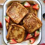 A baking pan filled with finished French toast surrounded by strawberries and spices.
