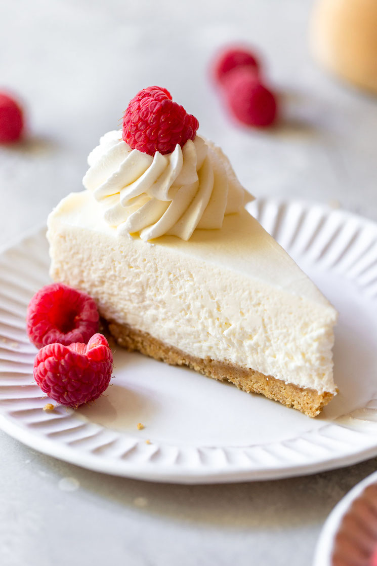 A single slice of no-bake cheesecake on a white plate topped with whipped cream and raspberries.