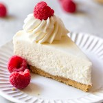 A single slice of no-bake cheesecake on a white plate topped with whipped cream and fresh raspberries.