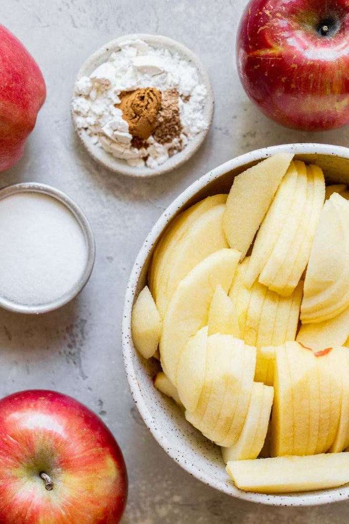 Apple crisp ingredients laid out on a rustic gray surface.