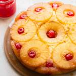A whole pineapple upside down cake on a plate with a jar of cherries in the background.