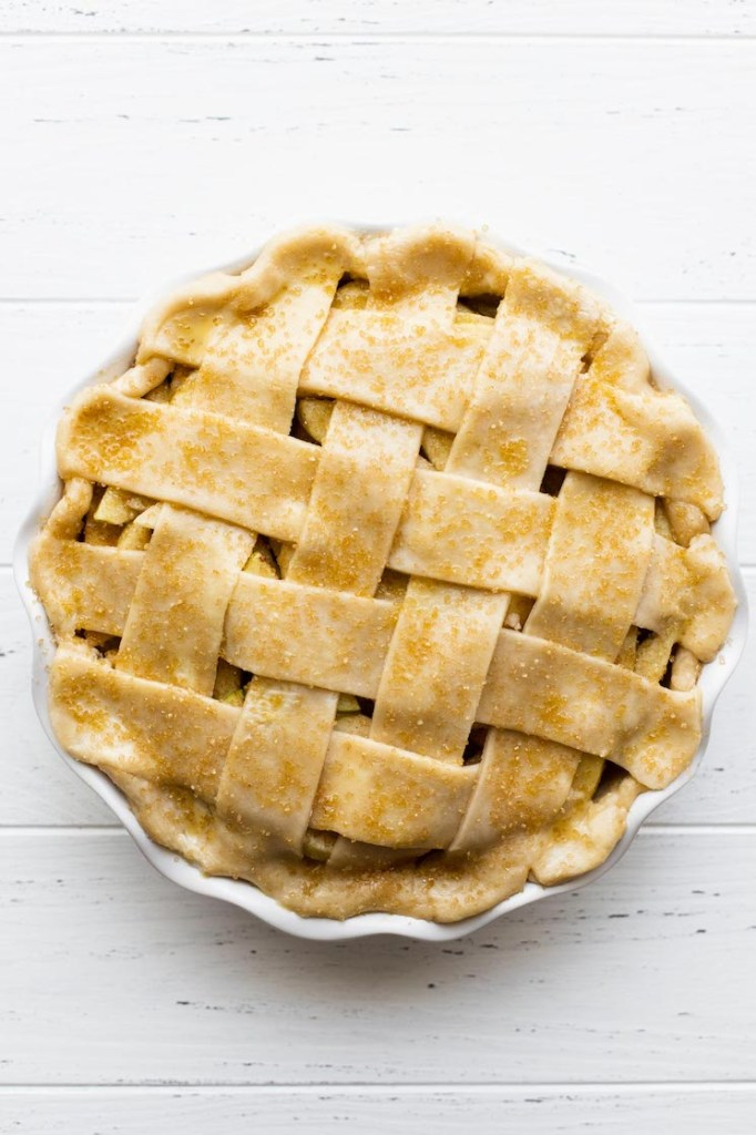 An apple pie topped with a lattice crust and coarse sugar ready to go into the oven.